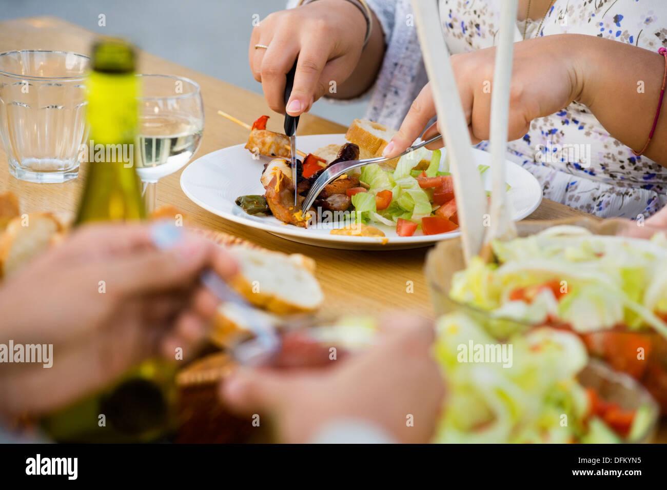 Sección media de la mujer cortando pedazo de carne en el plato en la mesa Imagen De Stock