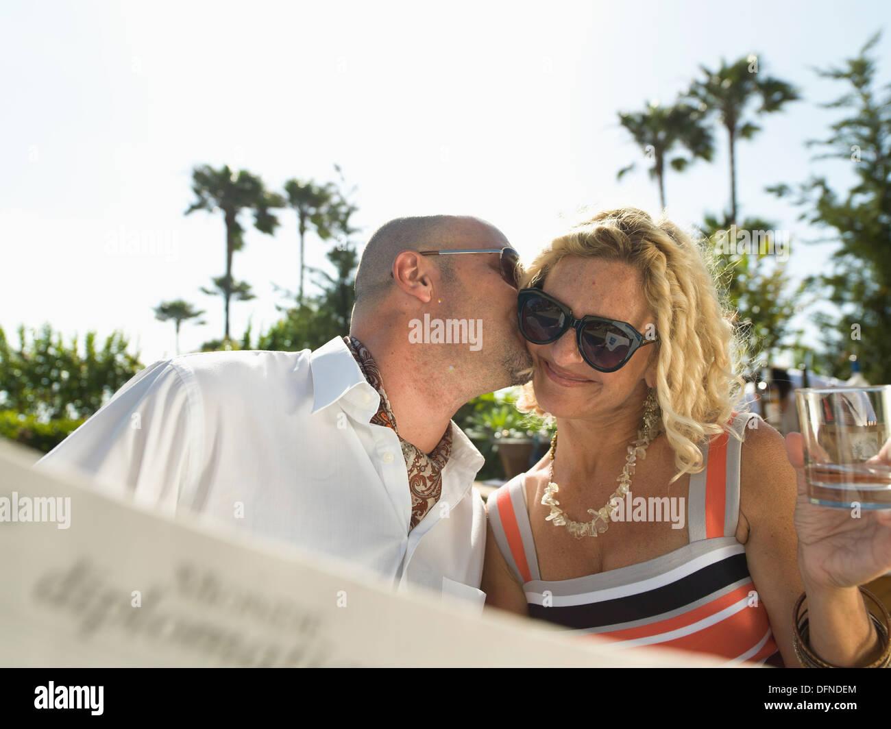 Un joven hombre besa el polluelo de una bella dama al lado de la piscina en San Diego. Imagen De Stock