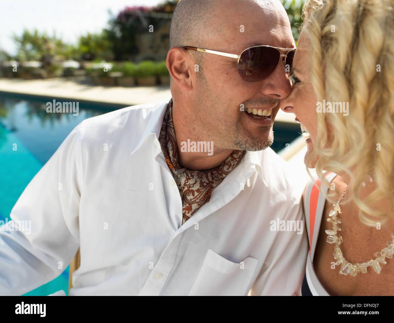 Un bien construido joven toca la punta de la nariz de una mujer bonita por su punta por el lado de la piscina en San Diego. Imagen De Stock
