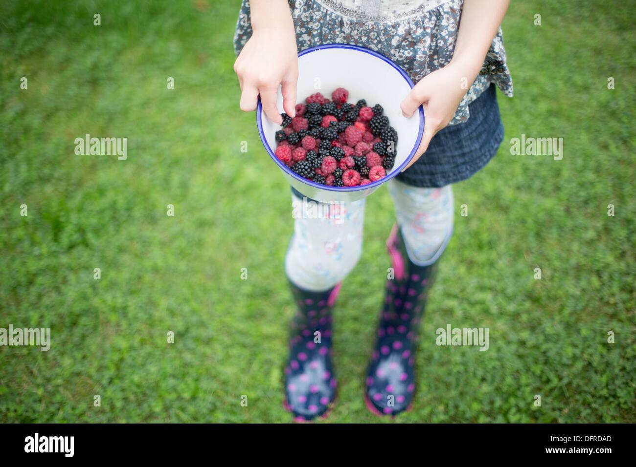 Chica sujetando el tazón lleno de frambuesas y moras Imagen De Stock