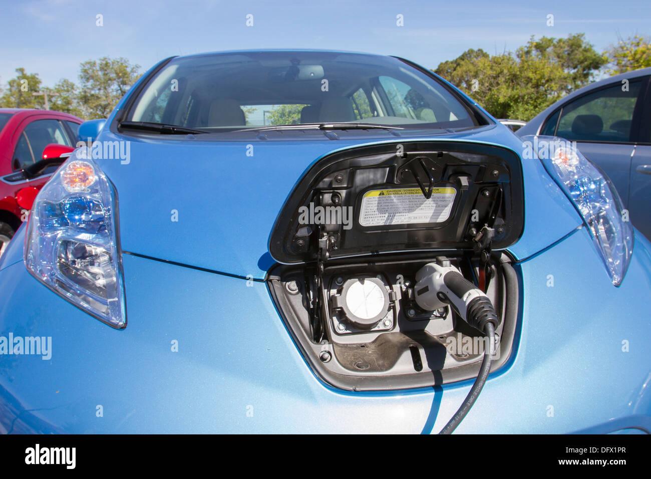 Azul coche eléctrico plug-in con el conector enchufado en una estación de carga para cargar su batería Imagen De Stock