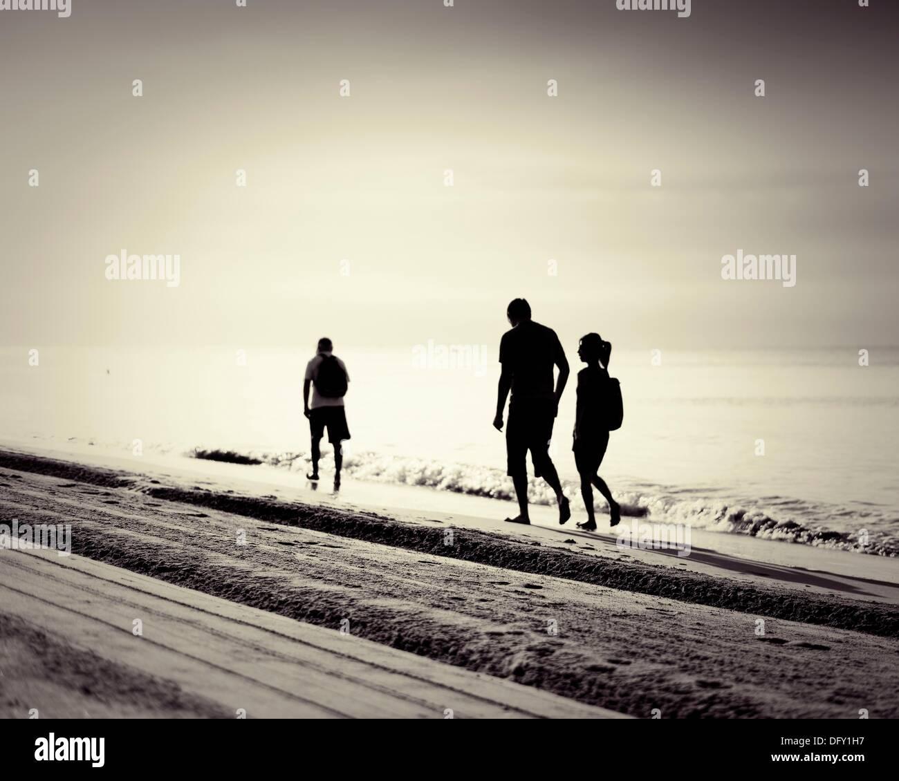 Los caminantes por el mar al amanecer Mar Mediterráneo Costa Dorada, ESPAÑA Imagen De Stock