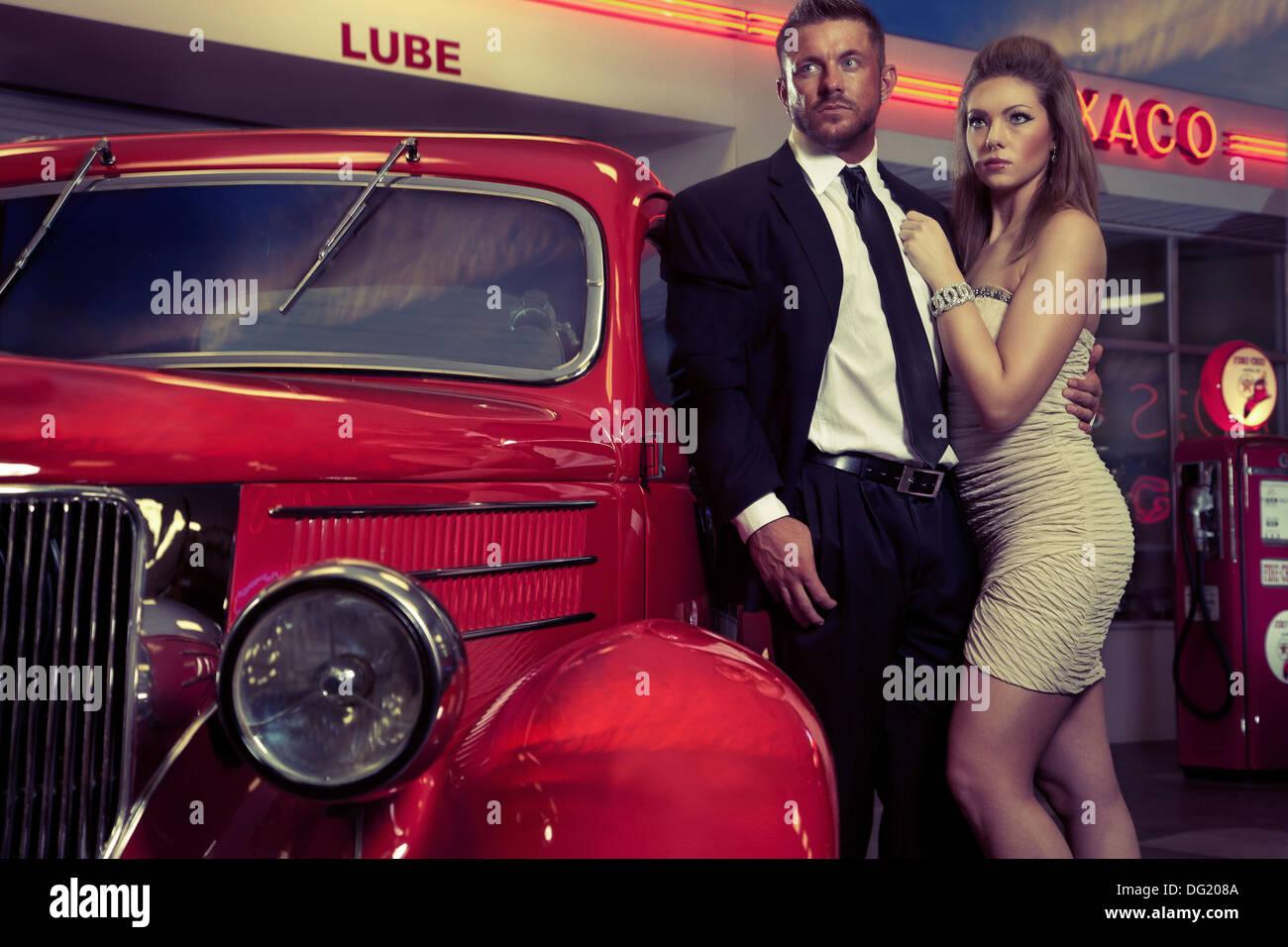 Bien vestidos al hombre y a la mujer junto al antiguo coche rojo en frente de la estación de servicio Imagen De Stock