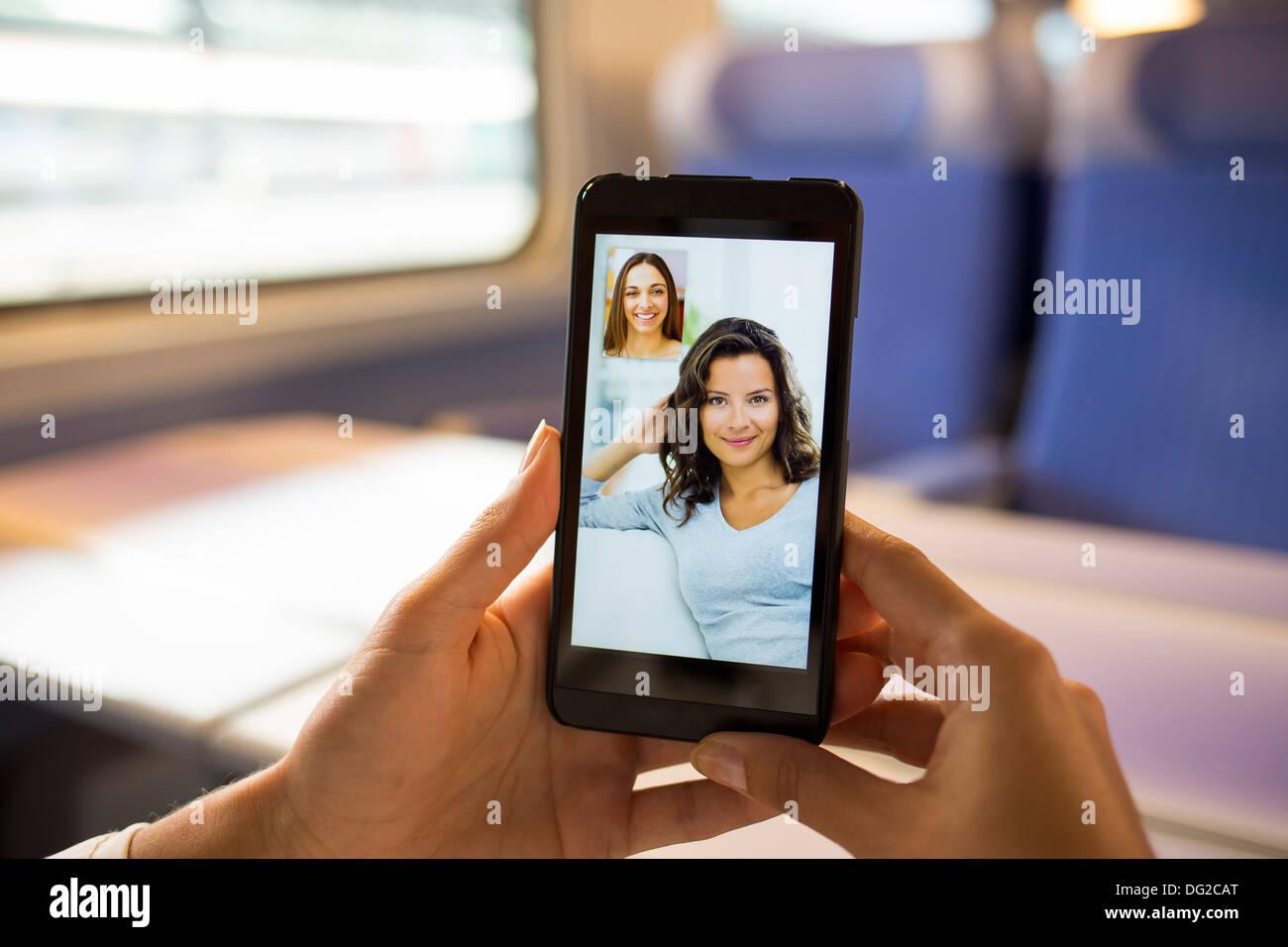 Mujer en el tren chateando en su teléfono móvil. Conferencia de vídeo Imagen De Stock