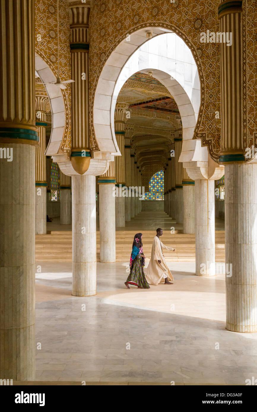 Senegal, Touba. Salones de oración para multitudes de desbordamiento en la Gran Mezquita. Un hombre y una mujer caminando. Imagen De Stock