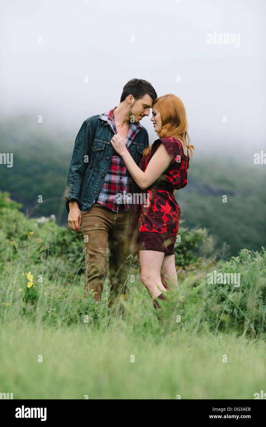 Pareja romántica de pie en campo neblinoso Imagen De Stock
