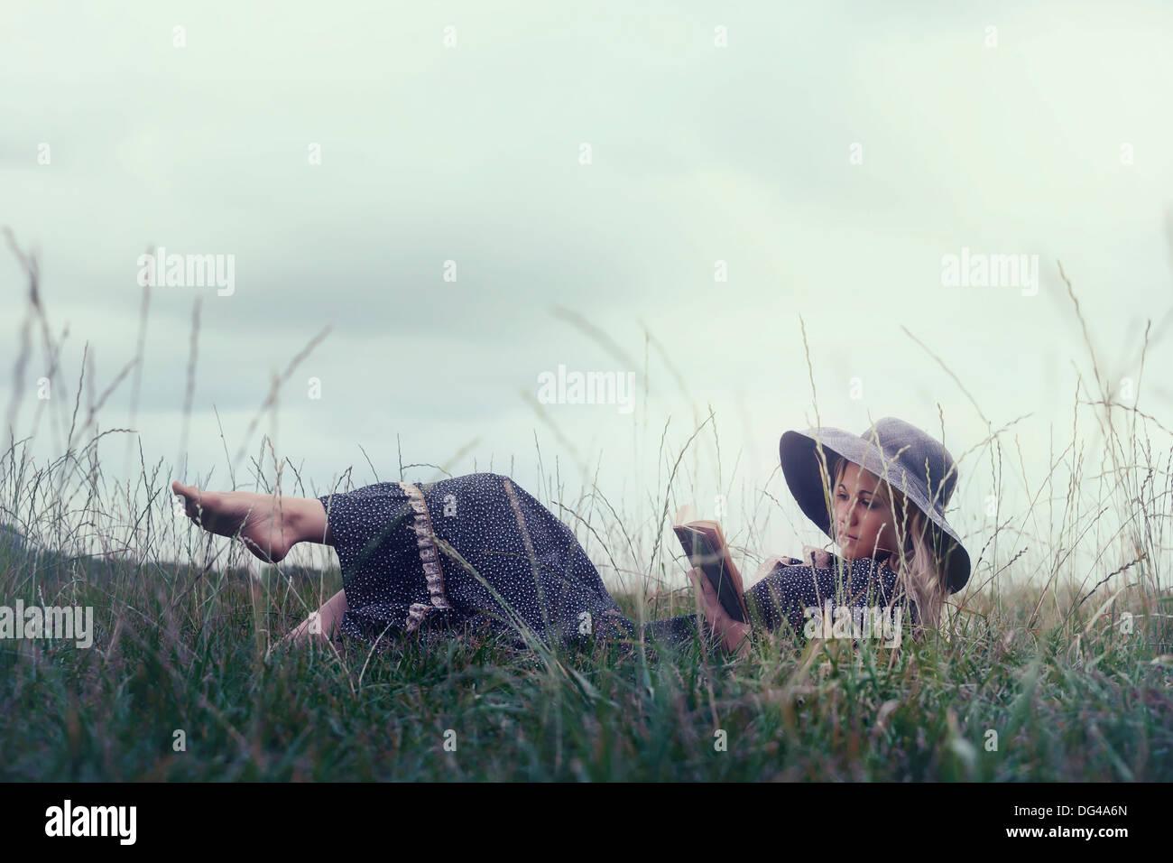 Una mujer en un romántico vestido está acostado sobre una pradera, leyendo un libro Imagen De Stock