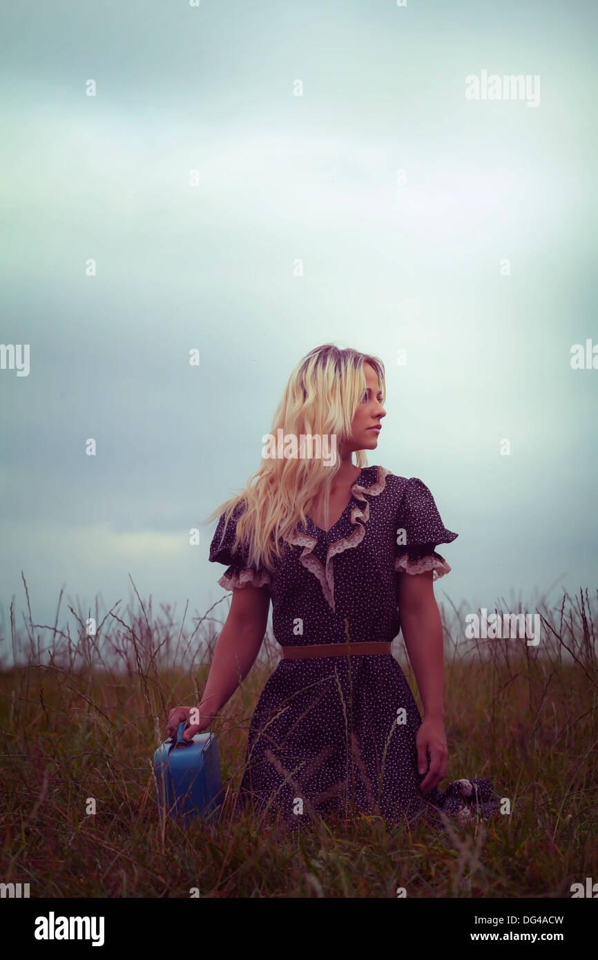 Una mujer en un romántico vestido en un prado con una maleta Imagen De Stock