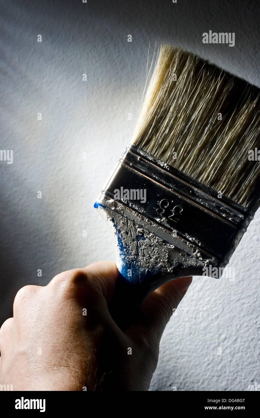 Detalle de una mano usando pincel de pintar Imagen De Stock