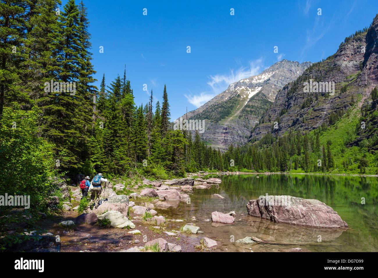 Los excursionistas en la orilla del lago de avalancha, el parque nacional de Glacier, Montana, EE.UU. Imagen De Stock