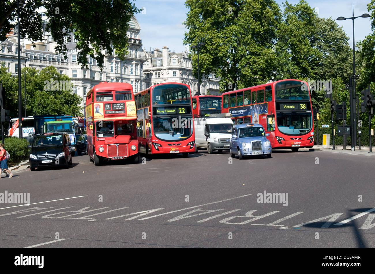 Una mezcla de los autobuses y los taxis se alejan de un semáforo en la esquina de Hyde Park, Londres. Imagen De Stock