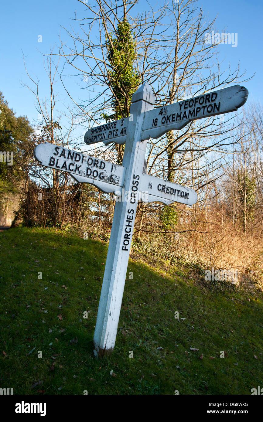 Antigua dirección firmar en blanco y negro cerca de Crediton, Devon, Inglaterra, mostrando la forma de un poblado llamado perro negro Imagen De Stock
