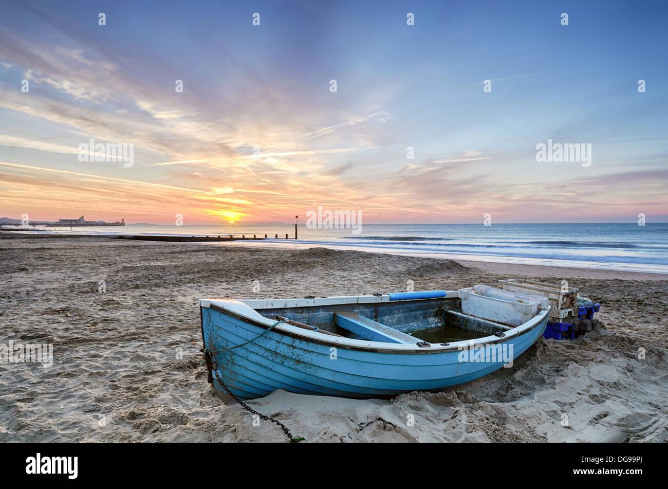 El azul turquesa del barco de pesca al amanecer en la playa de Bournemouth con muelle en la lejanía Imagen De Stock