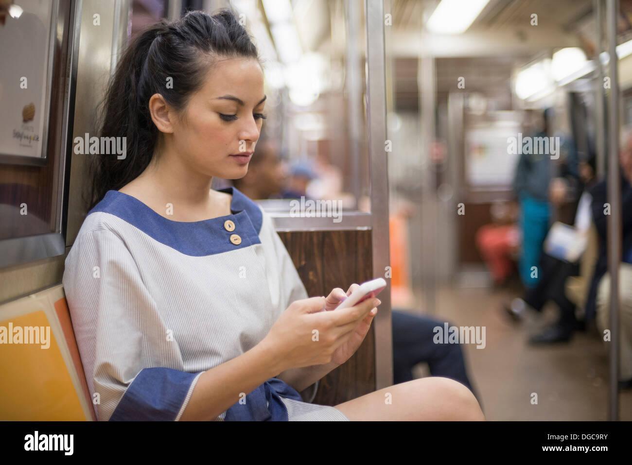 Mediados de mujeres adultas a través de teléfono móvil en el metro de Nueva York Foto de stock