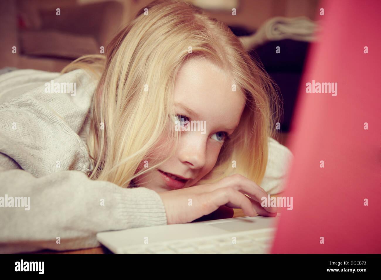 Joven acostado en el piso utilizando el portátil Imagen De Stock