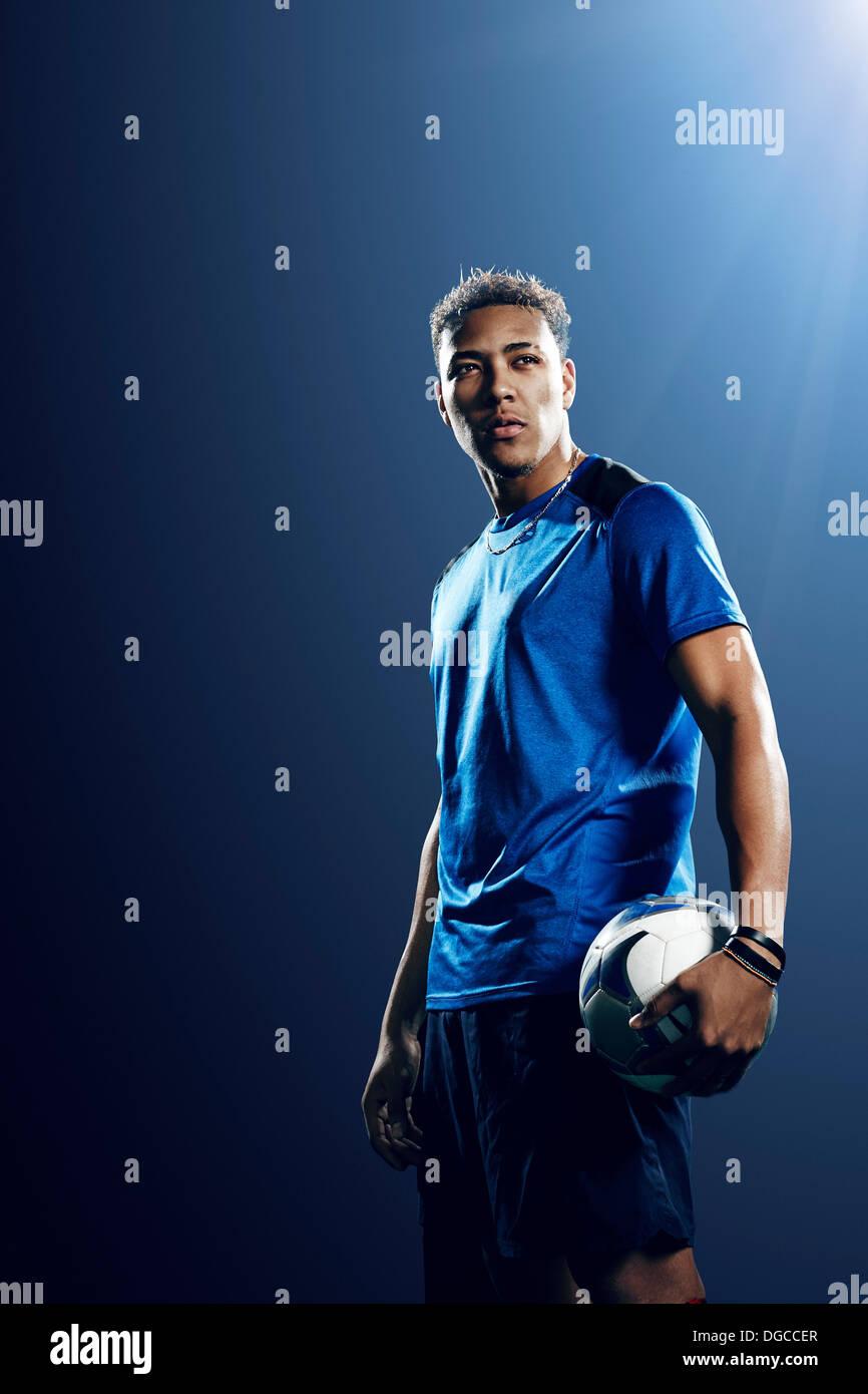 Retrato del jugador de fútbol masculino con el fútbol Foto de stock
