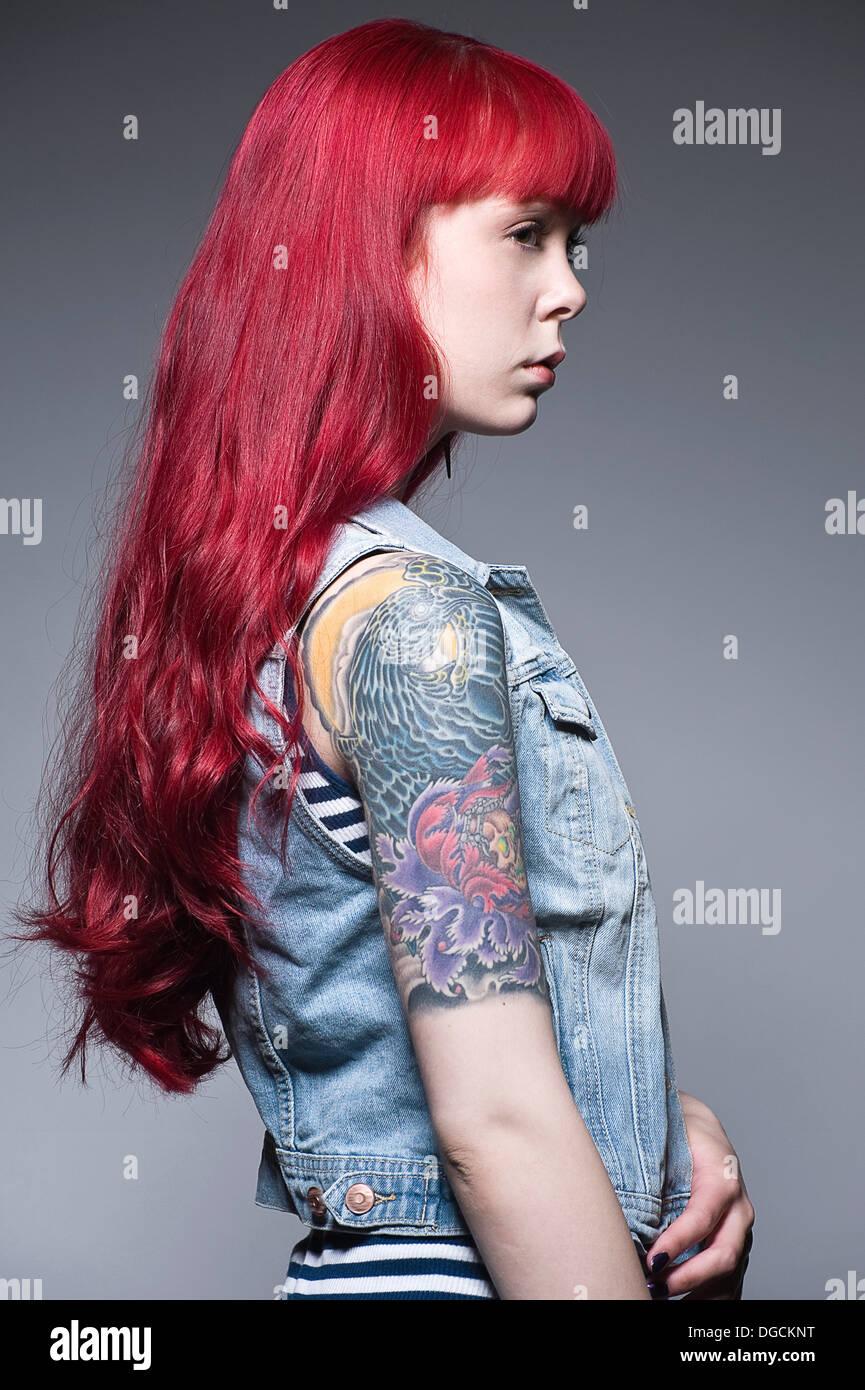 Mujer joven con largo pelo rojo y tatuajes, perfil Imagen De Stock