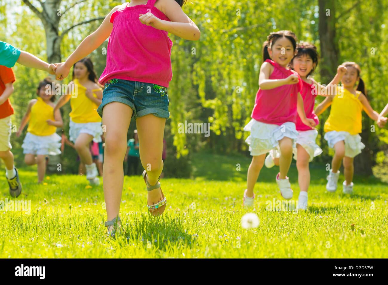 Niños corriendo sobre el césped Imagen De Stock