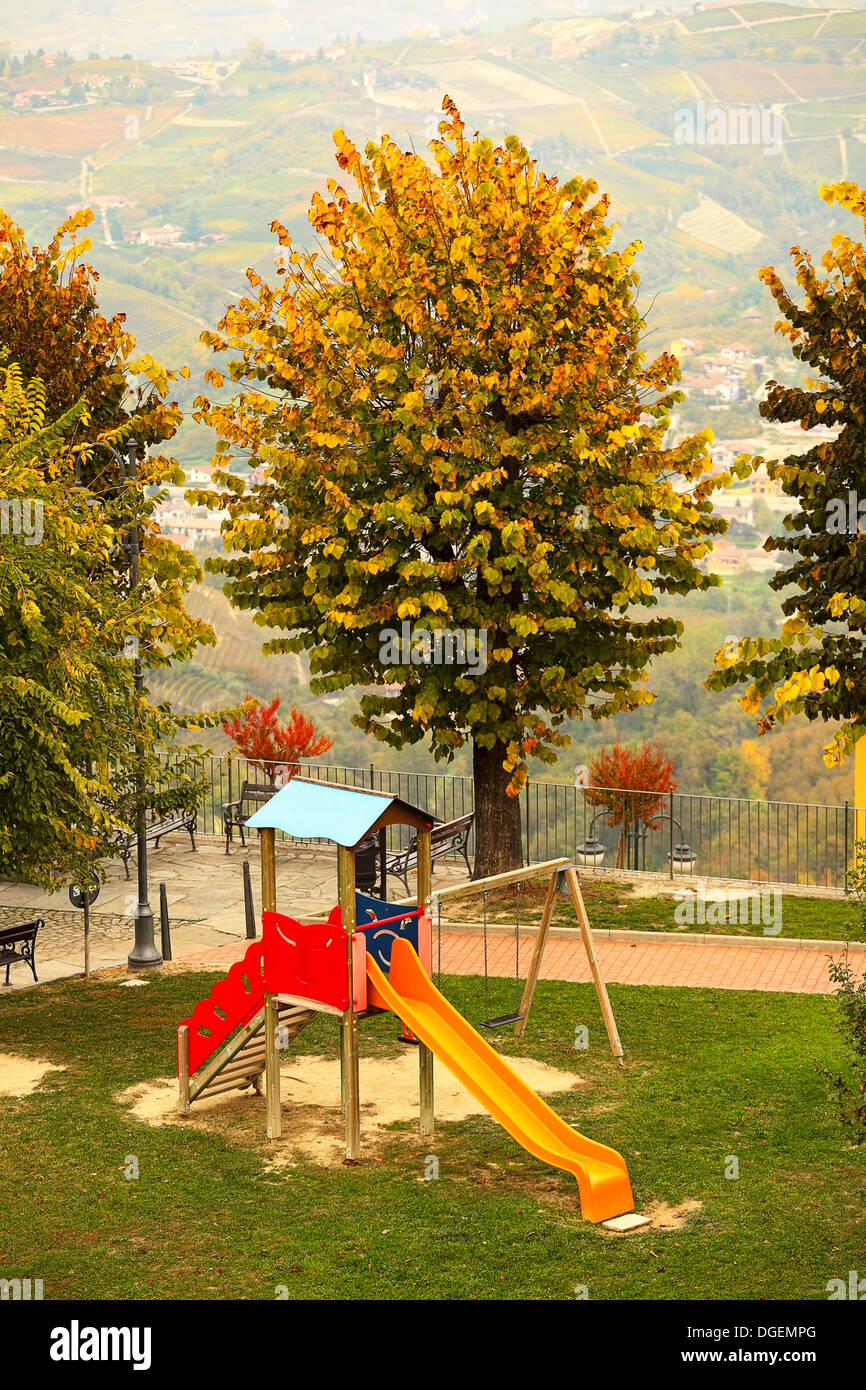 Los niños no acompañados en los vacíos de diapositivas del parque en otoño en la pequeña ciudad de Diano D'Alba, Italia. Imagen De Stock