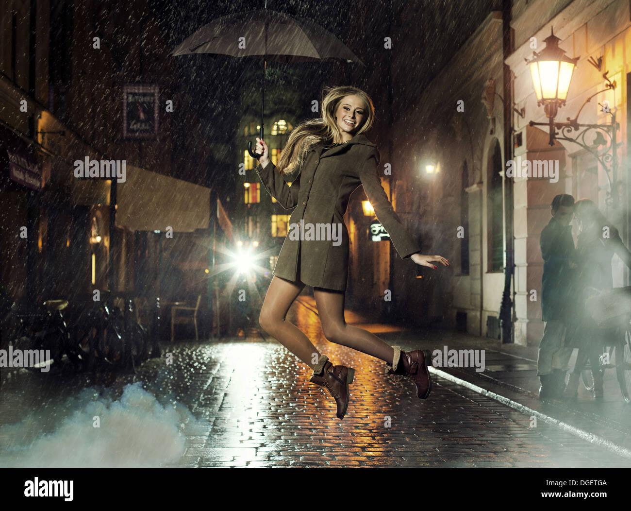 Foto fantástica de atractiva dama saltando en Heavy Rain Imagen De Stock