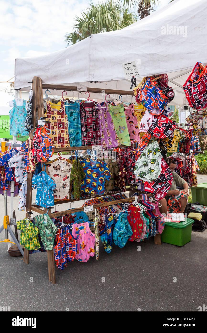 Colorida ropa de niños en la pantalla de la tienda del proveedor en el festival de artes y oficios. Imagen De Stock
