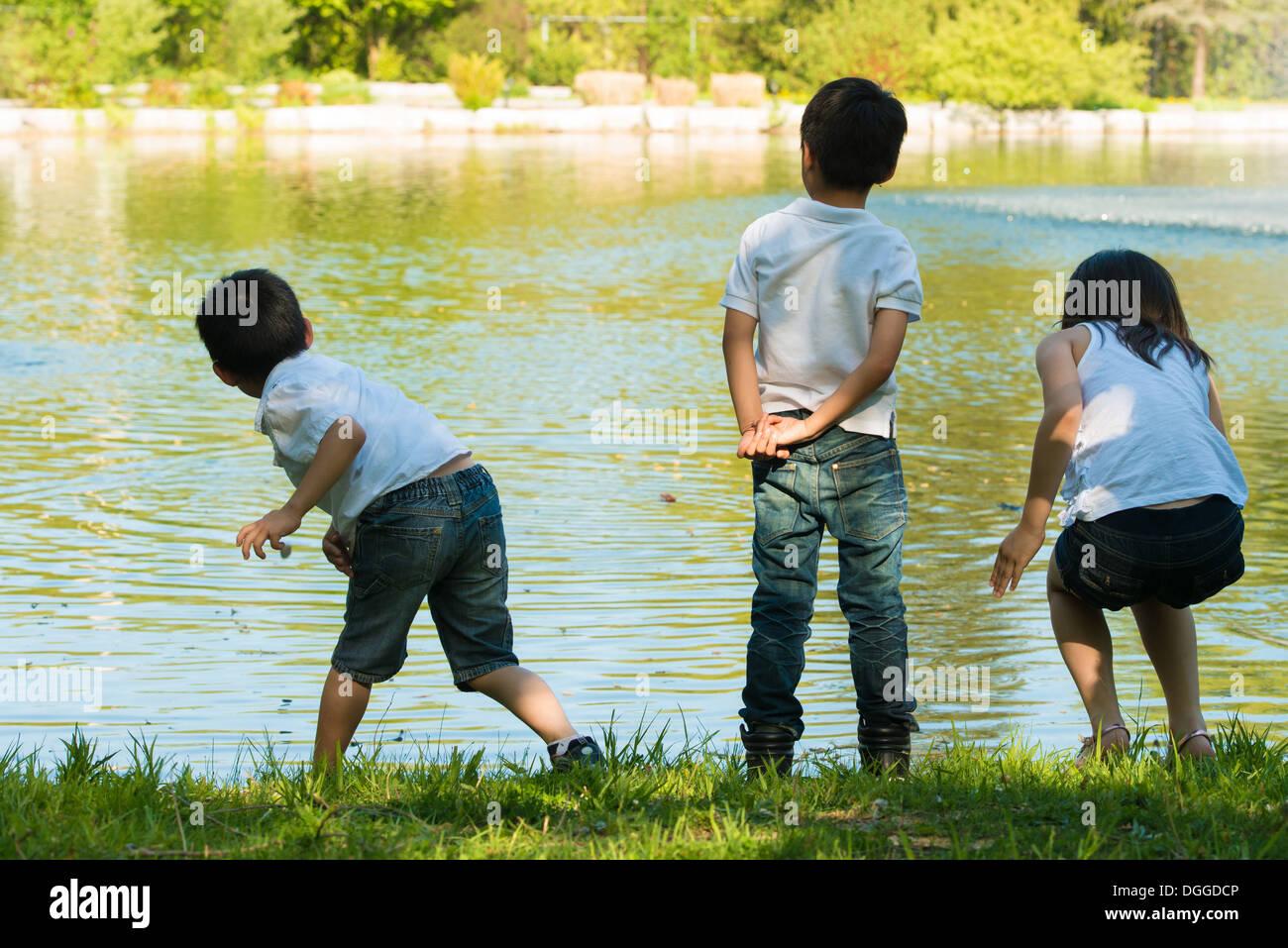 Tres niños jugando junto al lago Imagen De Stock