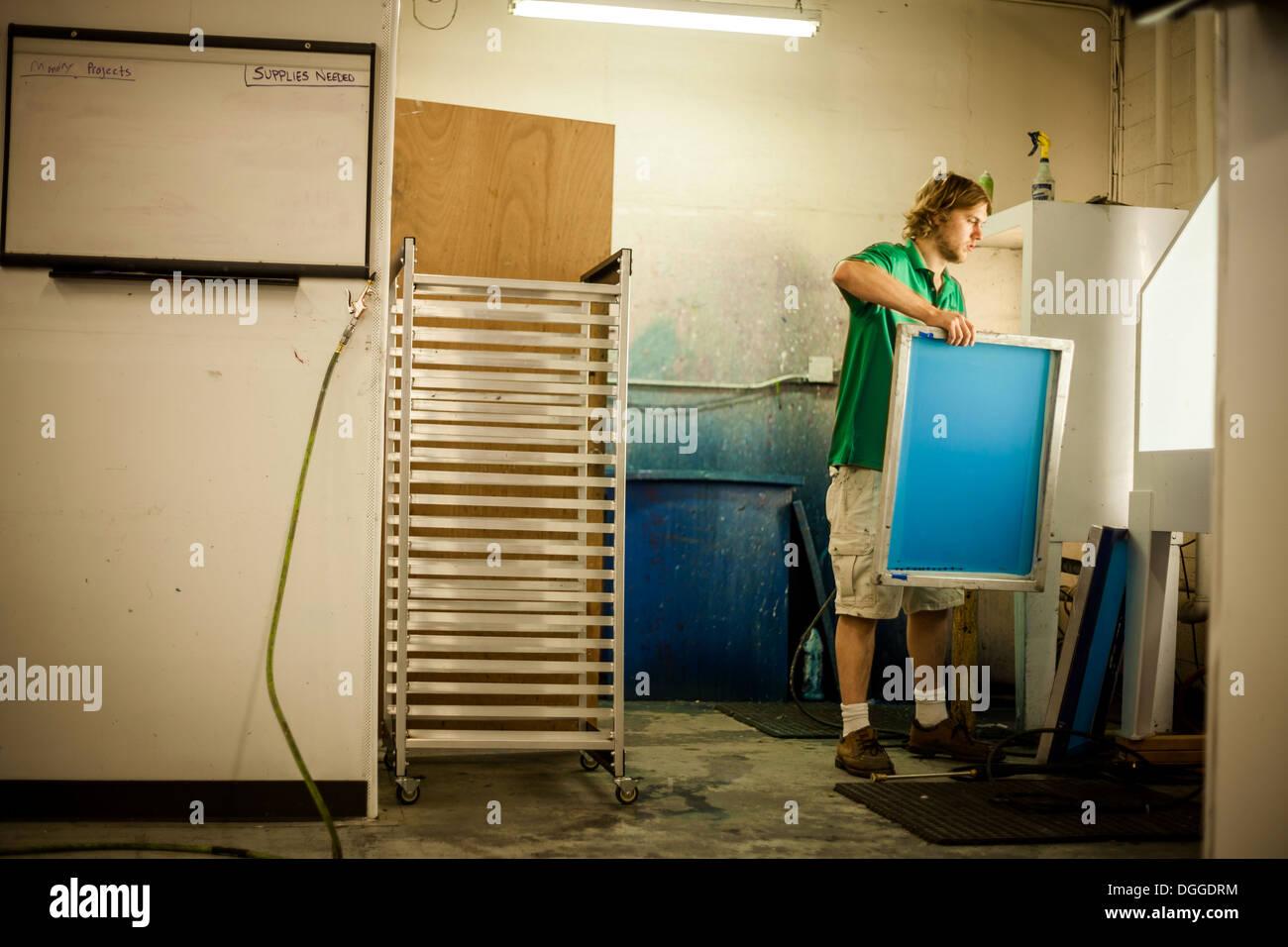 El hombre que sostiene el bastidor en el taller de impresión de pantalla Imagen De Stock