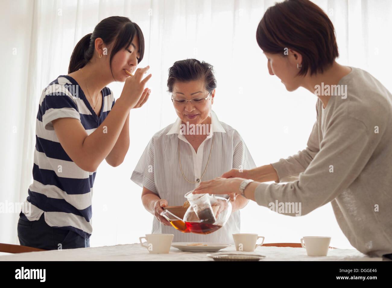 Tres generaciones de la familia té vertido Foto de stock