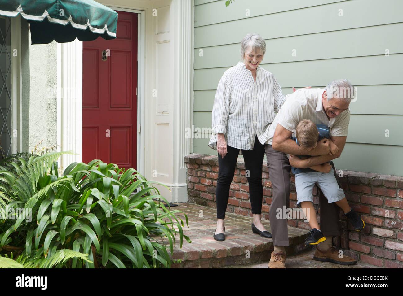 Hombre Senior jugando con su nieto fuera de casa Foto de stock