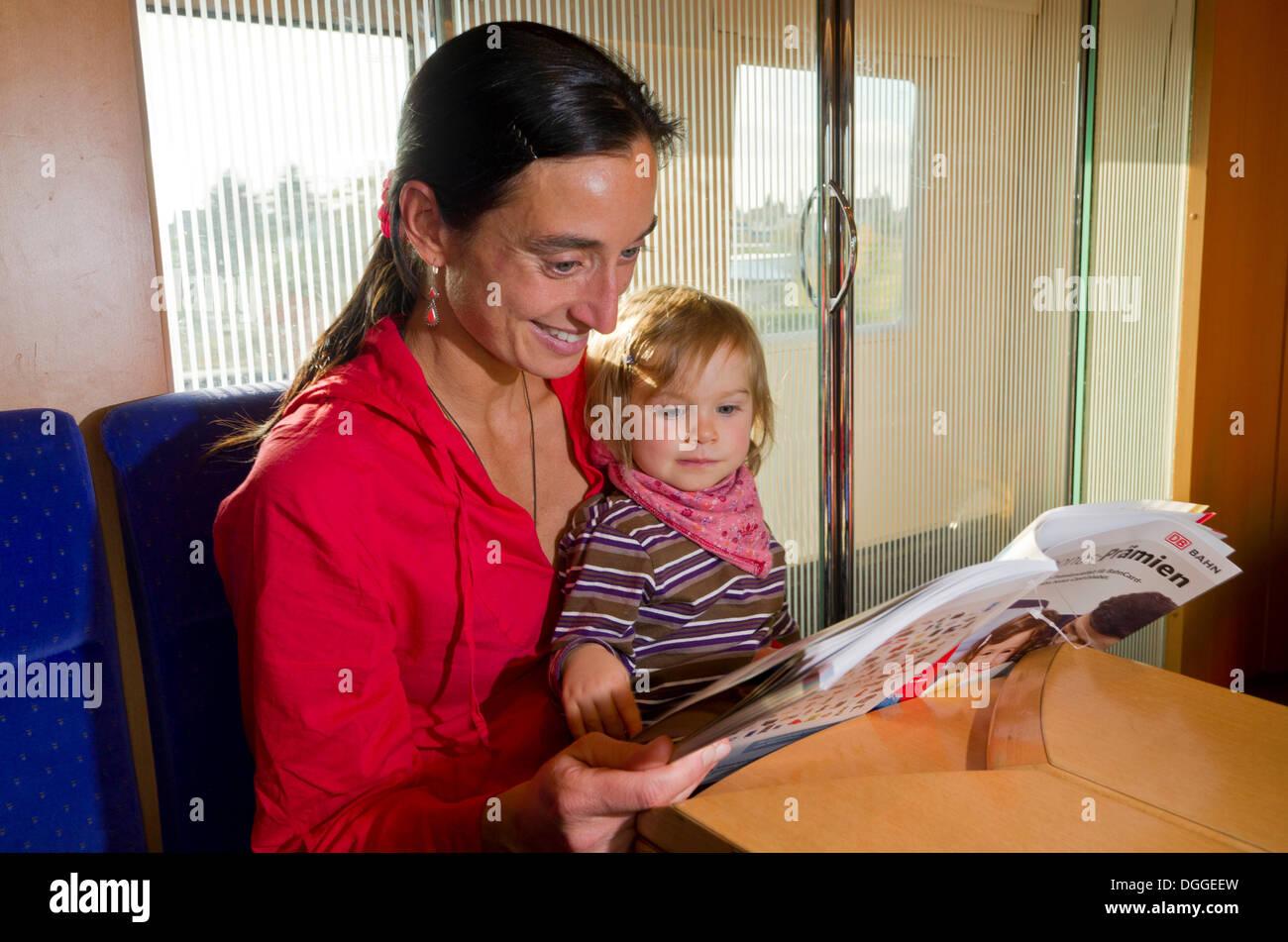 Joven madre con su hijo la lectura en un libreto interior tren ICE, Dresde, Sajonia, Alemania Foto de stock