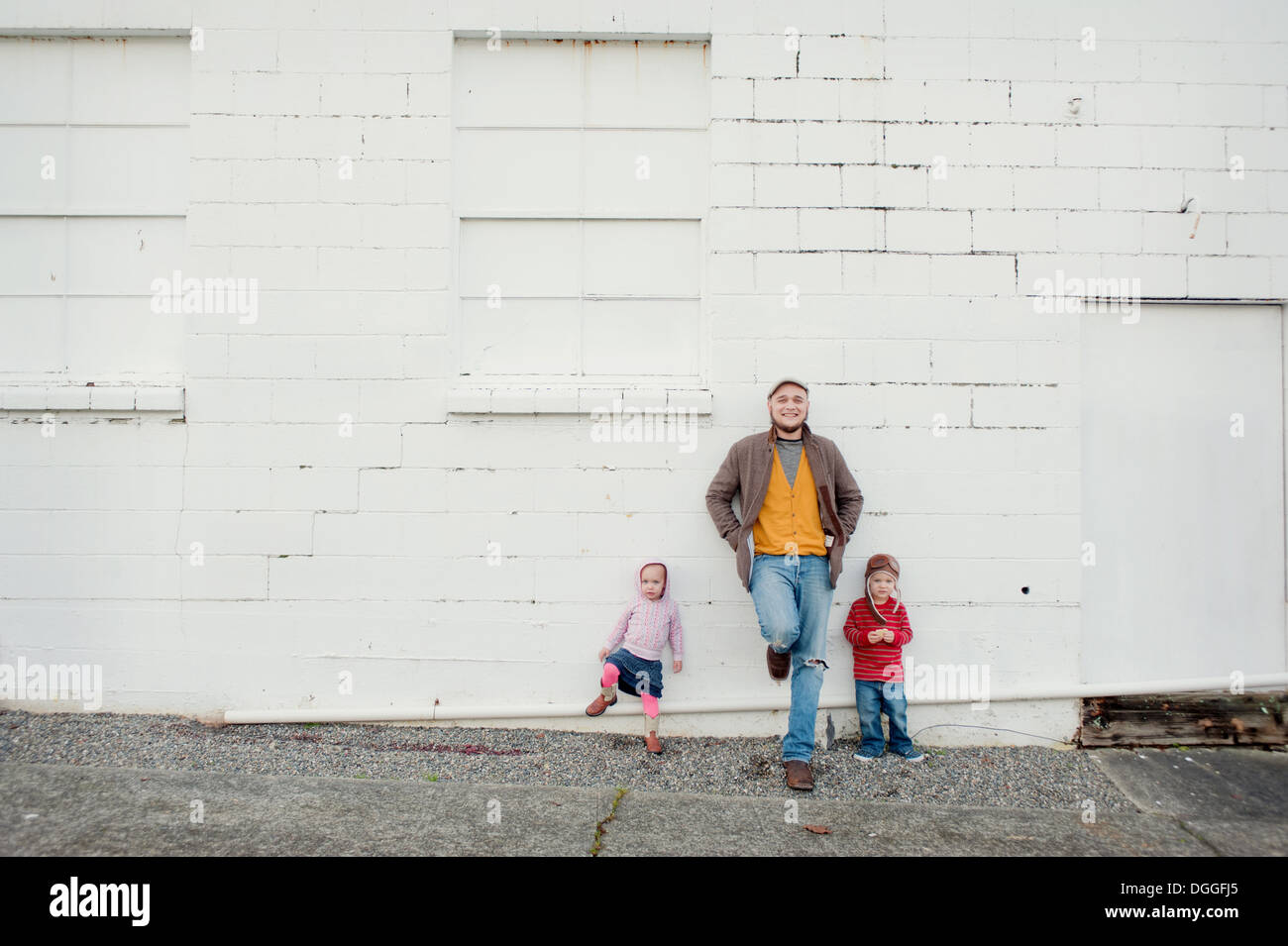 Mitad hombre adulto y su hijo e hija recostada contra la pared, Retrato Imagen De Stock