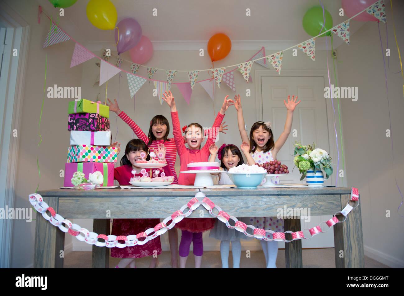 Las niñas vitoreando en fiesta de cumpleaños Imagen De Stock