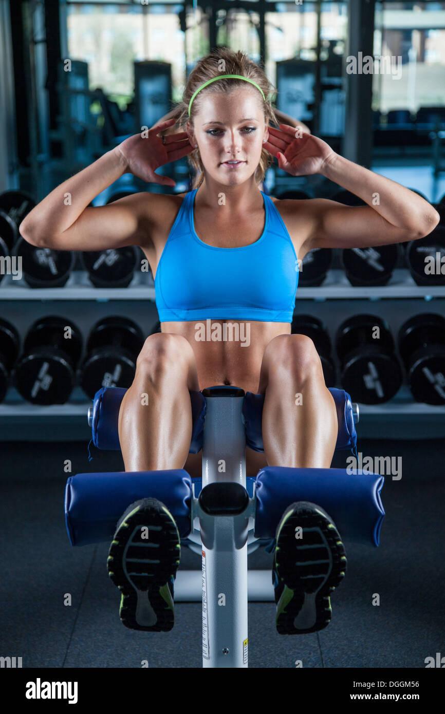 Mujer joven haciendo sentarse ups en el gimnasio Imagen De Stock