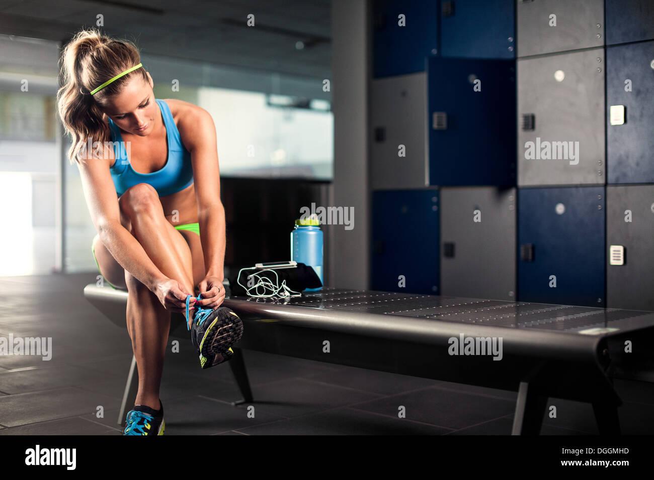 Mujer joven entrenador atado puntilla en gimnasio Imagen De Stock