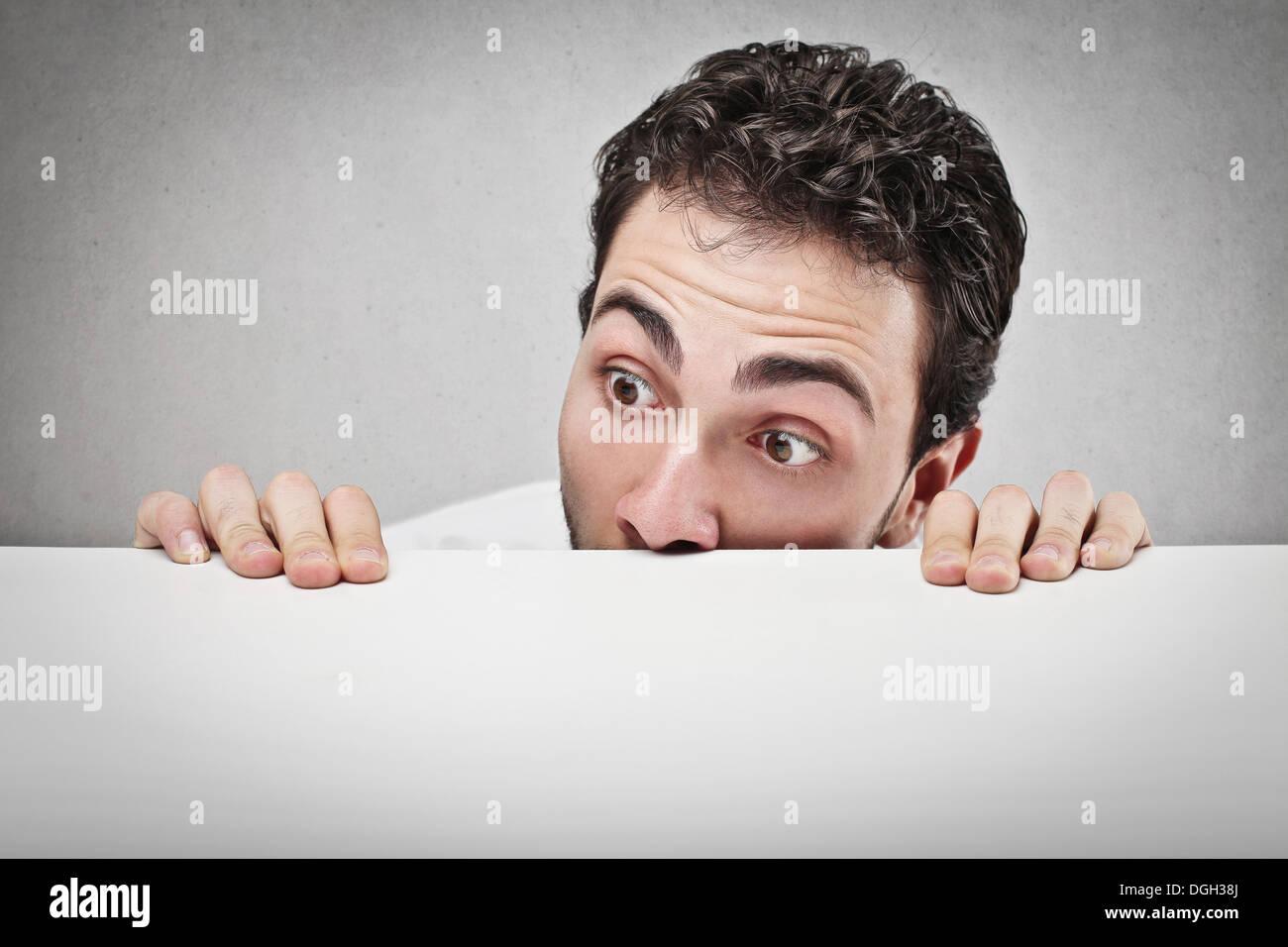 Sorprendido el hombre viendo algo sobre un mostrador blanco Imagen De Stock