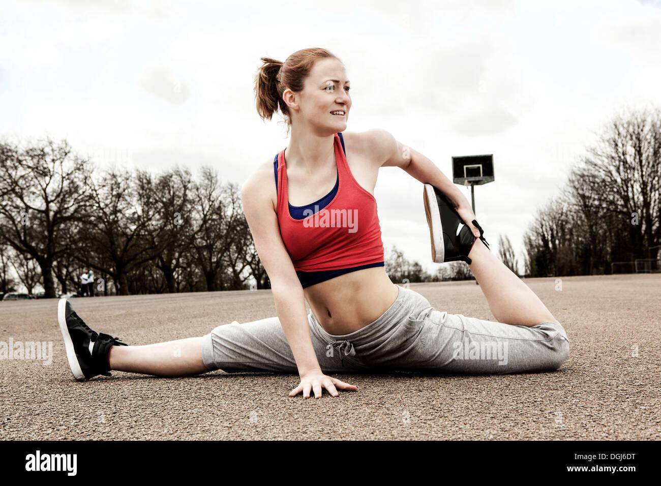 Mujer haciendo divisiones con la pierna izquierda doblada hacia atrás Imagen De Stock