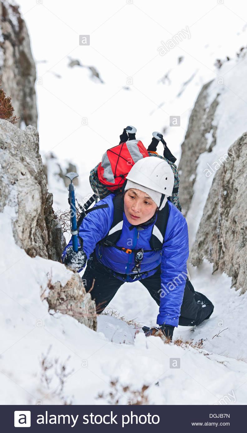 Escalador femenino viene a través de la nieve cubrió ravine, Castell y Geifr, Snowdonia Imagen De Stock