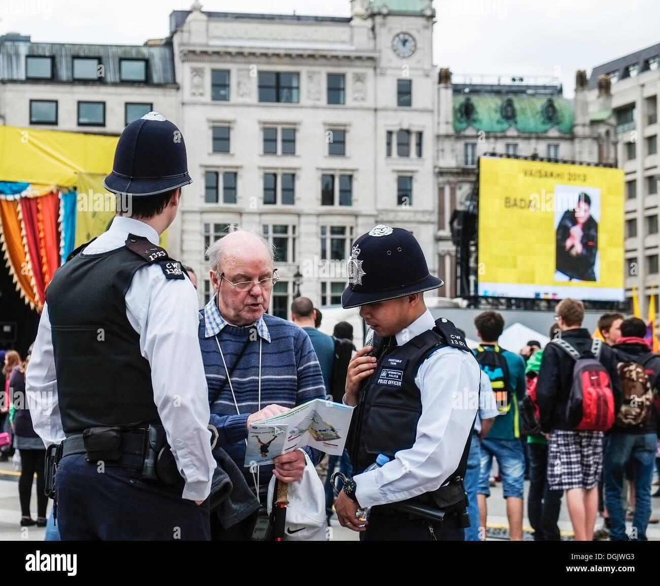 Dos funcionarios de la Policía Metropolitana ayudando a un turista. Imagen De Stock