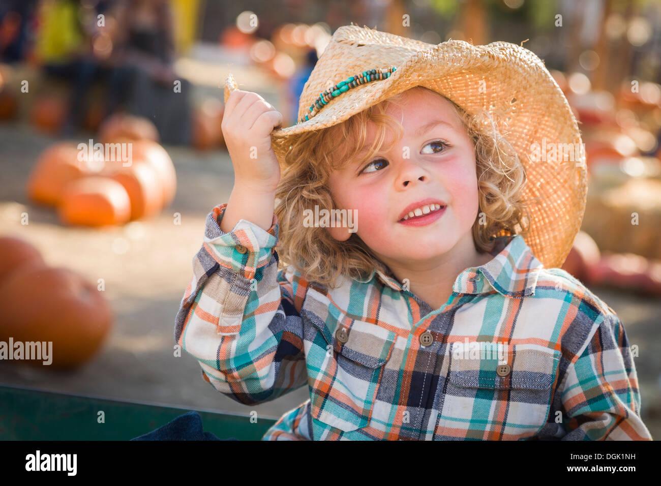 33f296066 Adorable pequeño niño usando sombrero de vaquero en Pumpkin Patch Farm.  Imagen De Stock