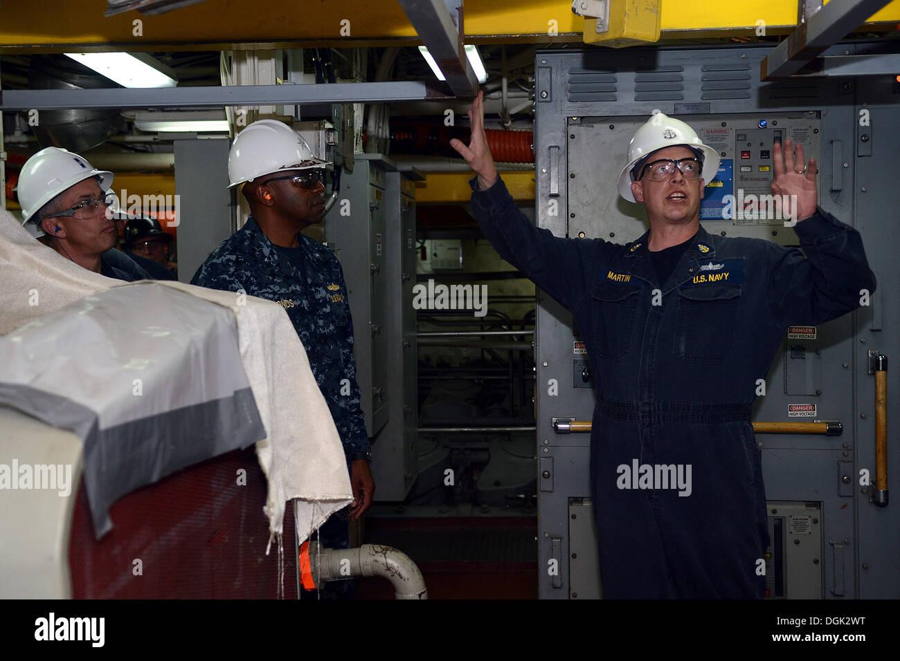 Jefe Senior Engineman Eric Martin explica las actualizaciones del motor previsto del buque al Comandante del Grupo de ataque expedicionario (ESG) 3 Trasero Adm. Frank estanque durante una excursión a bordo del USS buque anfibio de transporte Dock Green Bay (LPD 20). Green Bay está en BAE Syst Foto de stock