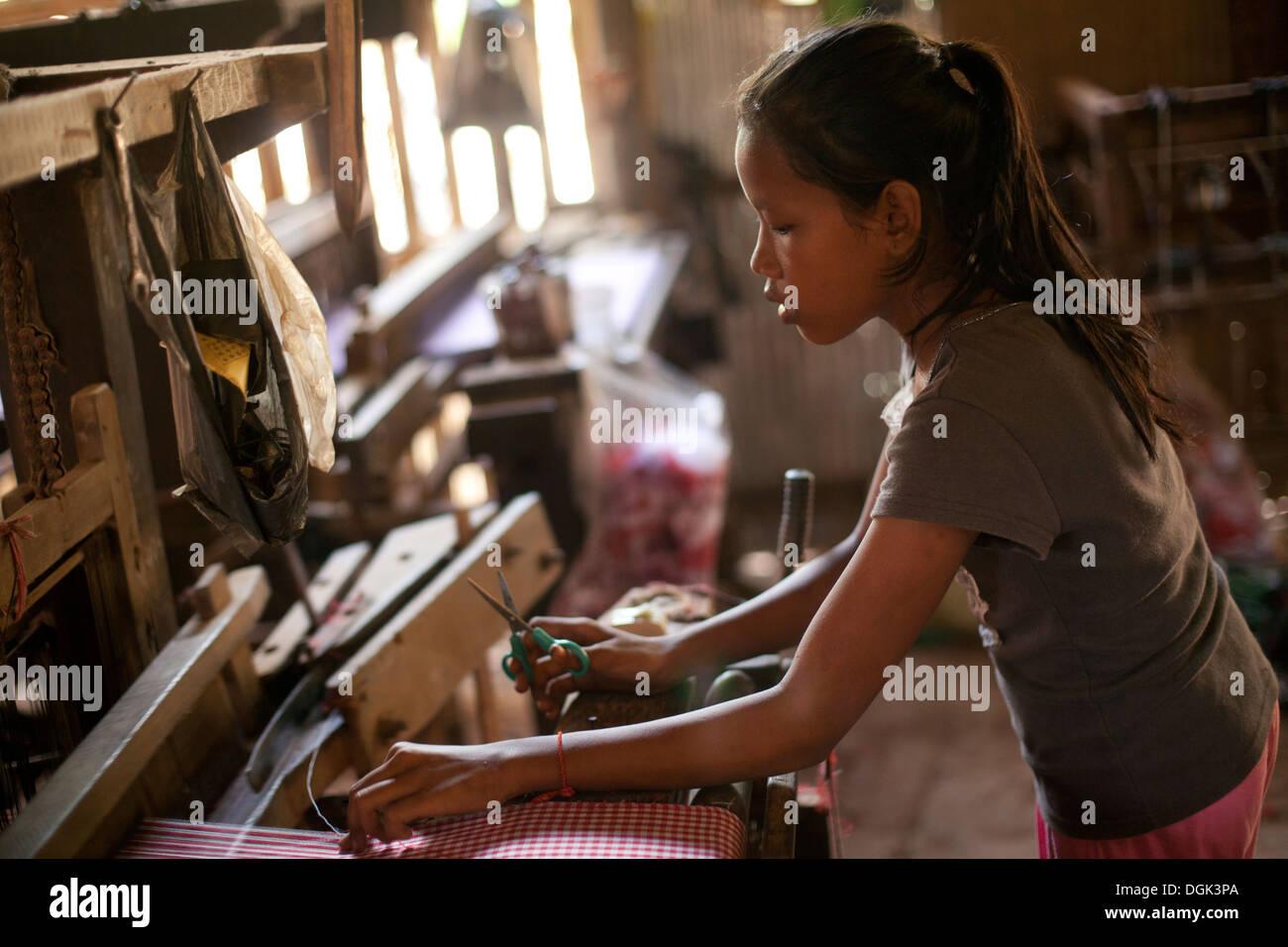 Una joven que trabaja en una fábrica textil de aldea fuera de Phnom Penh, Camboya. Dennis Drenner fotos © 2013. Imagen De Stock