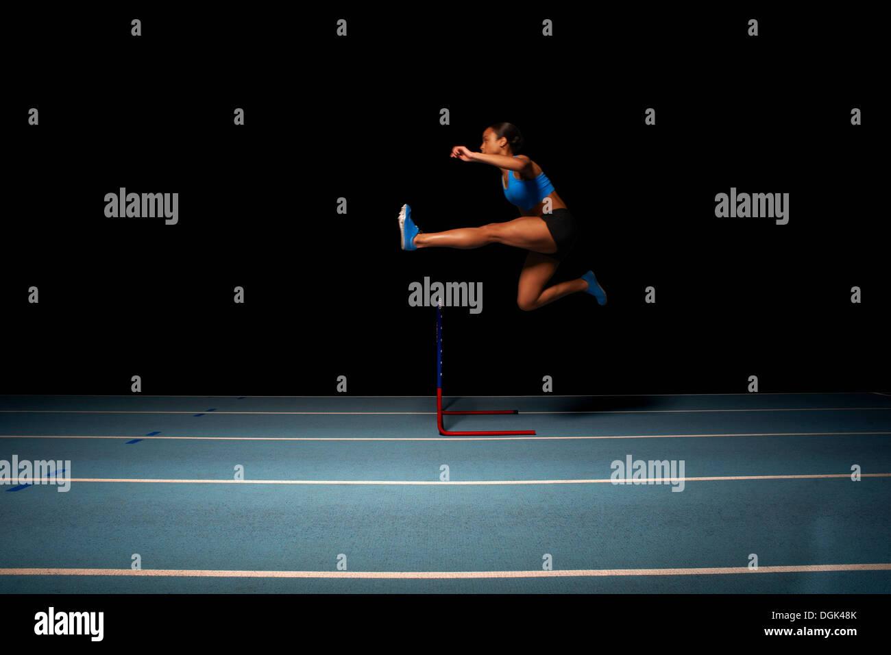 La atleta femenina joven saltando valla Imagen De Stock