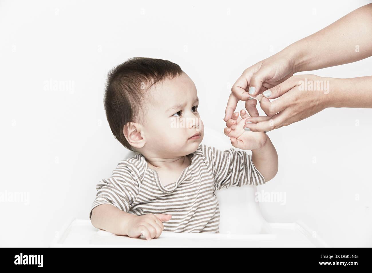 Manos aplicando la pasta a dedo del bebé Imagen De Stock