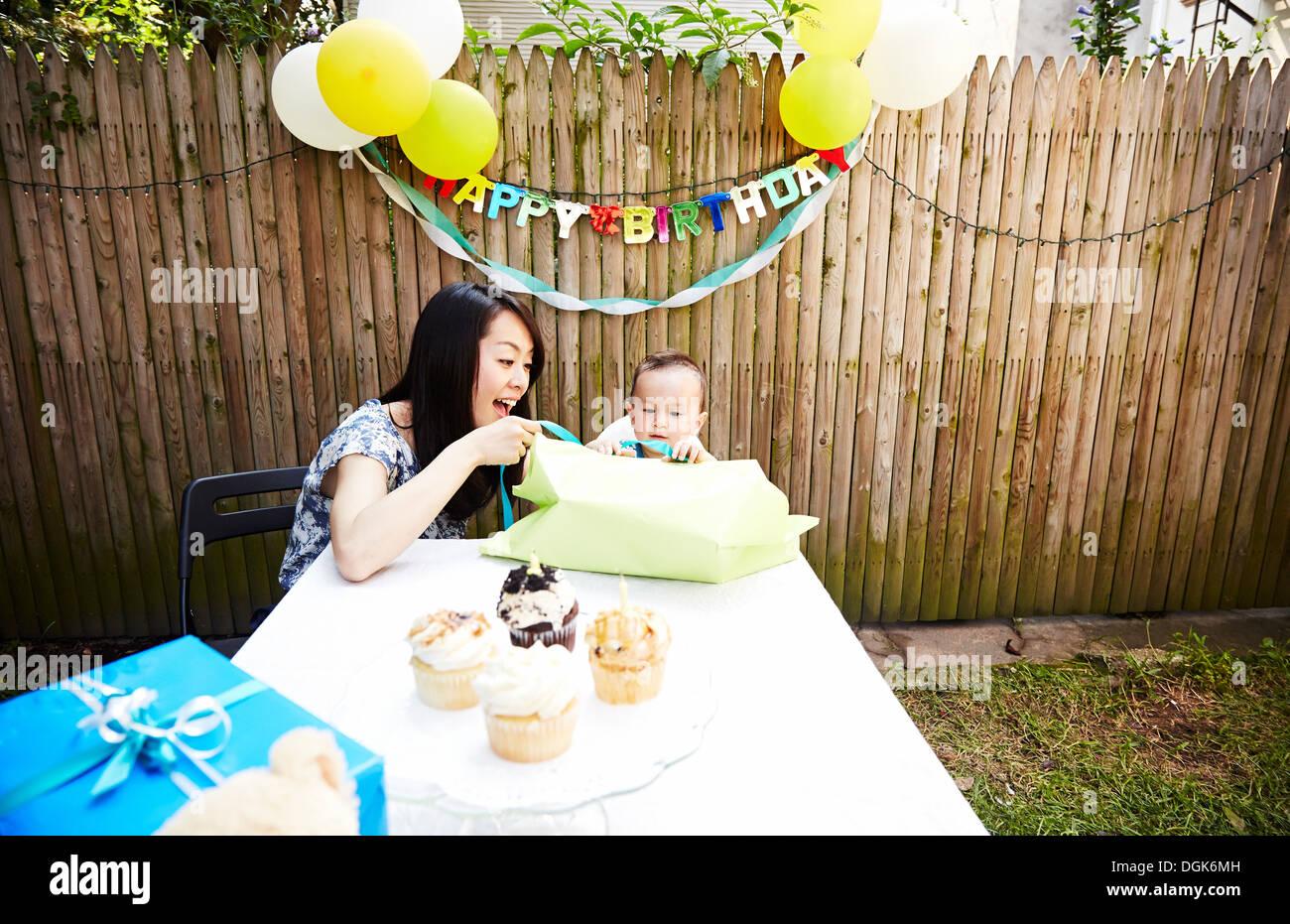 Madre y bebé niño desenvolver regalo de cumpleaños Imagen De Stock