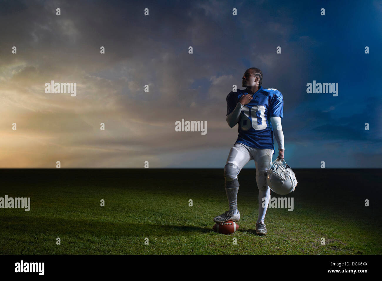 Retrato de jugador de fútbol americano descansando el pie sobre el balón Imagen De Stock