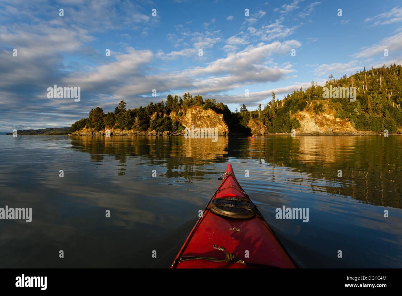 Kayak paddler jefes hacia la tierra en remotas zonas salvajes de Alaska en la soleada tarde en verano Foto de stock