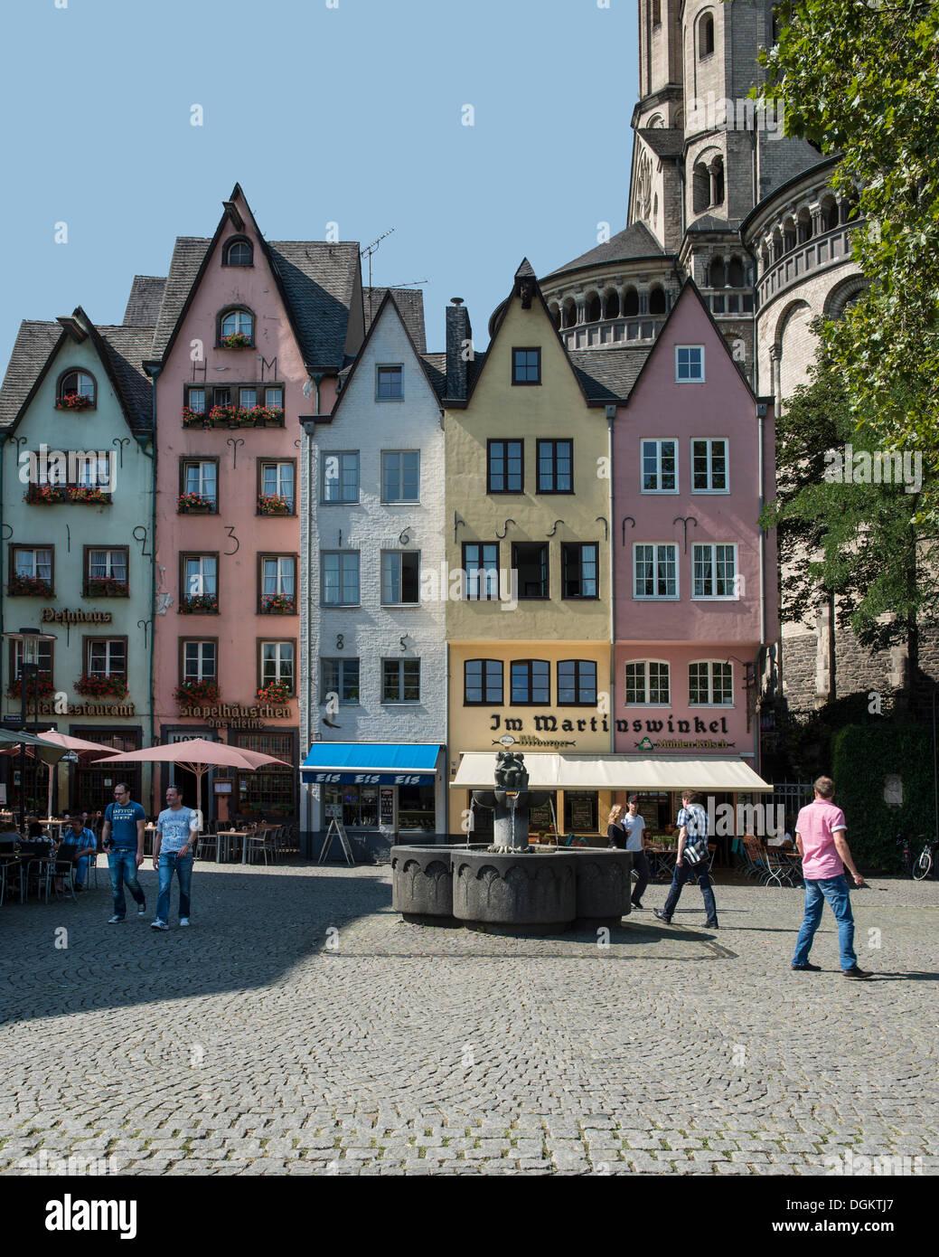 Hilera de coloridas casas en Martinswinkel, con la gran iglesia románica de San Martín en la parte trasera, Am Fischmarkt Imagen De Stock