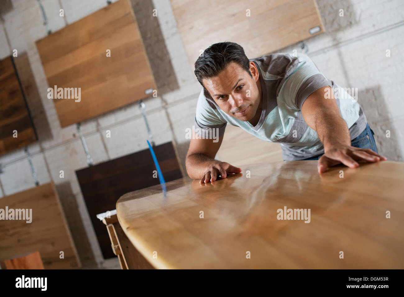 Un hombre joven en un taller con stock de maderas recicladas y regeneradas. Imagen De Stock