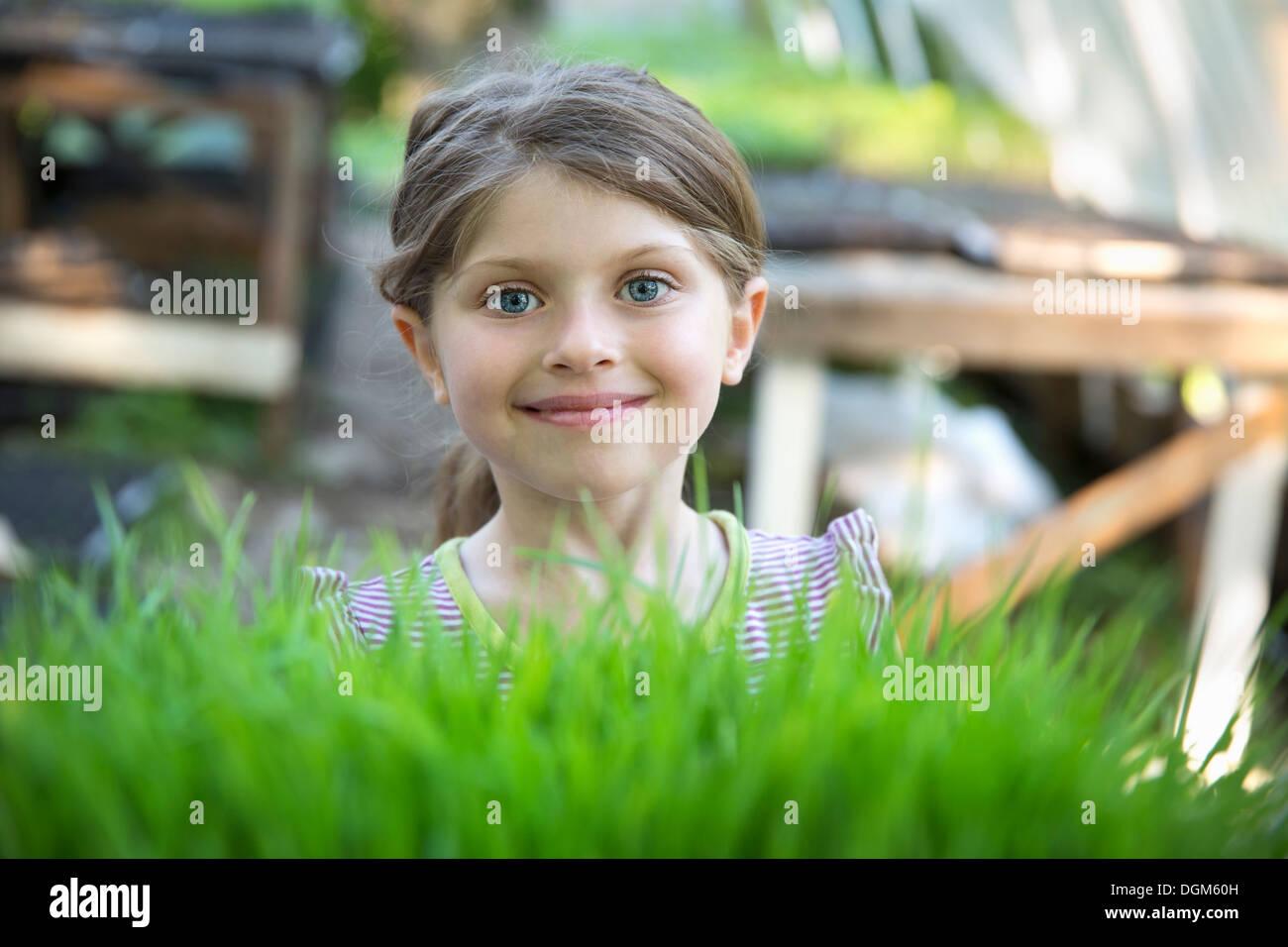 En la granja. Una niña sonriente permanente por una banqueta glasshouse mirando por encima de los brotes de plantas que crecen en las bandejas. Foto de stock
