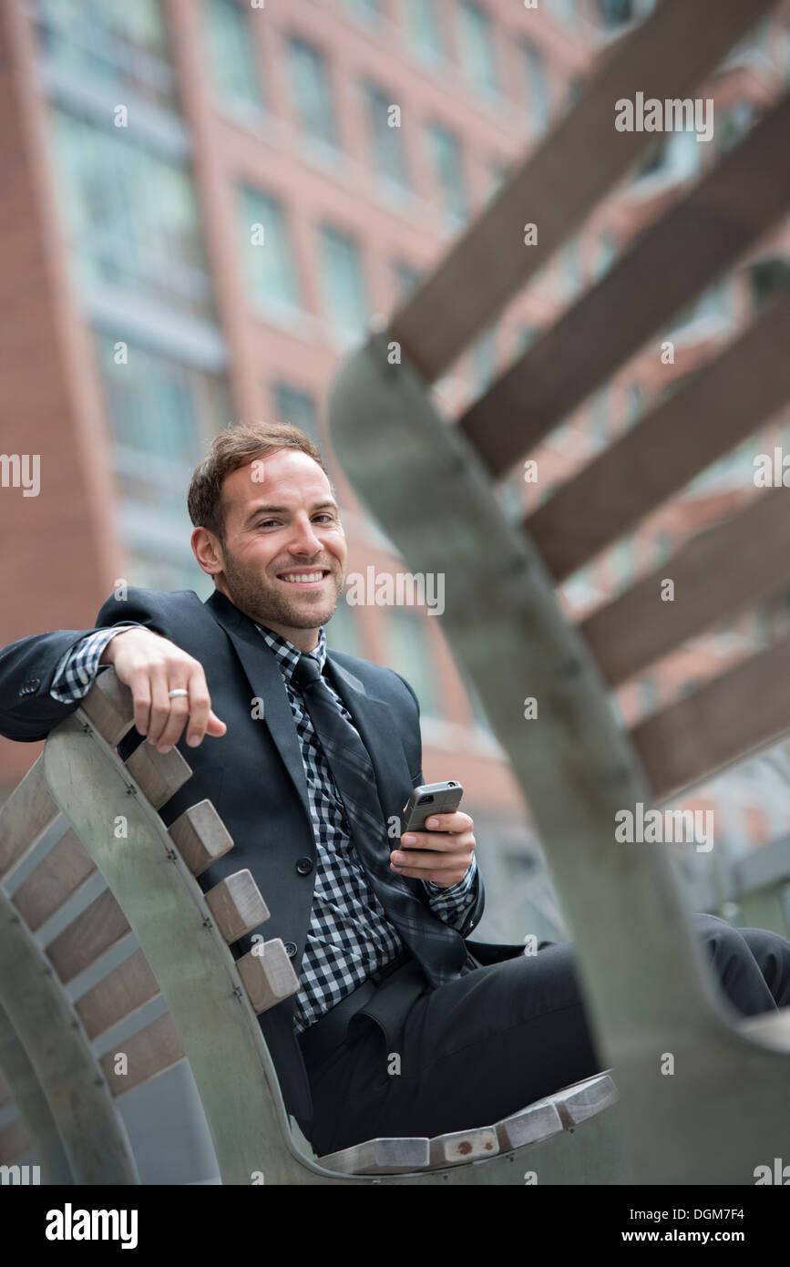 La gente de negocios. Un hombre en un traje, sentado en un banco. Foto de stock